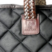 Alice Foxx Chelsea Bag in quilted black waxed cotton - close detail of leather handle and logo.